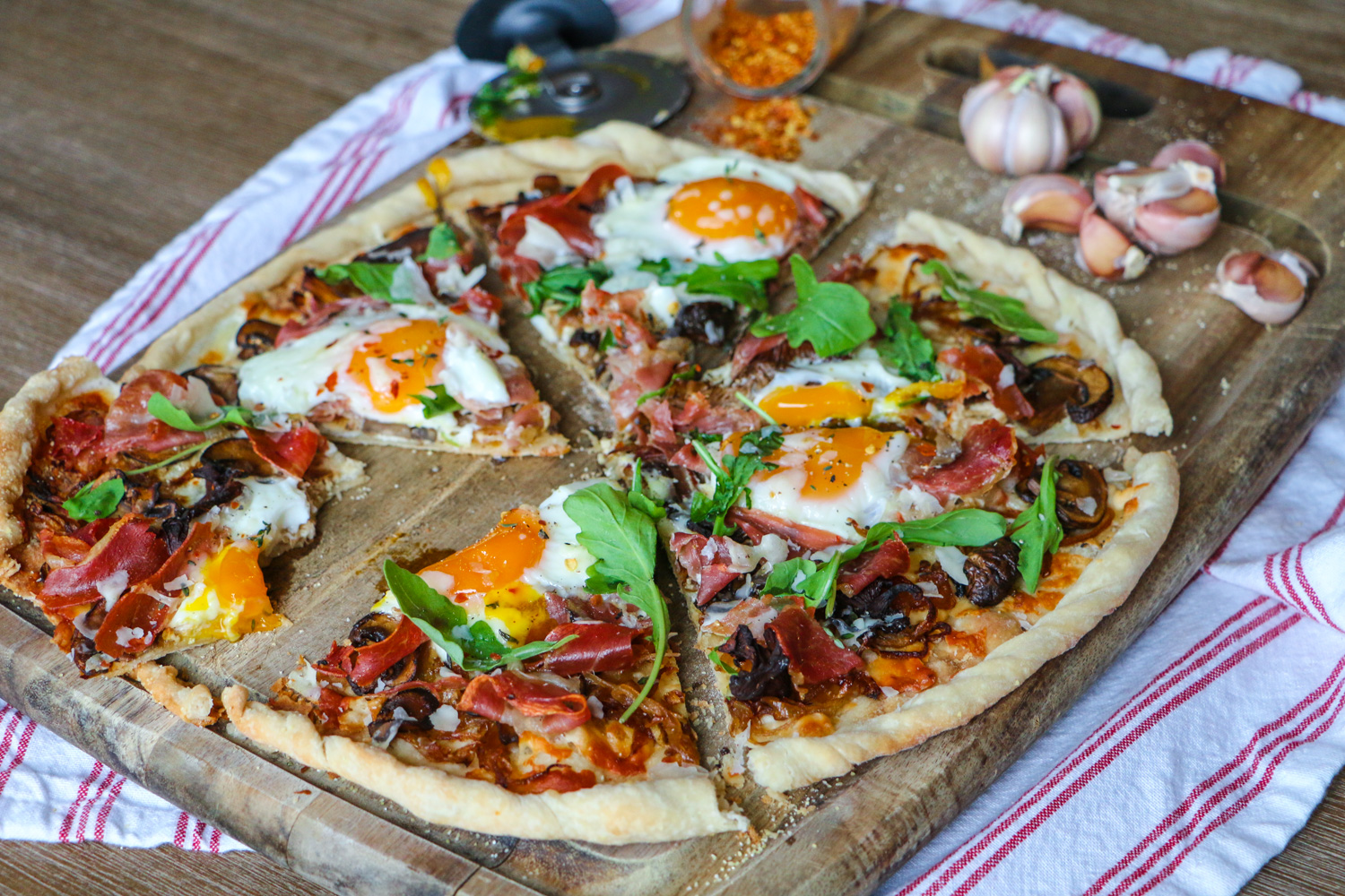 Breakfast pizza with arugula, soft bakes eggs, caramelized onions, and prosciutto