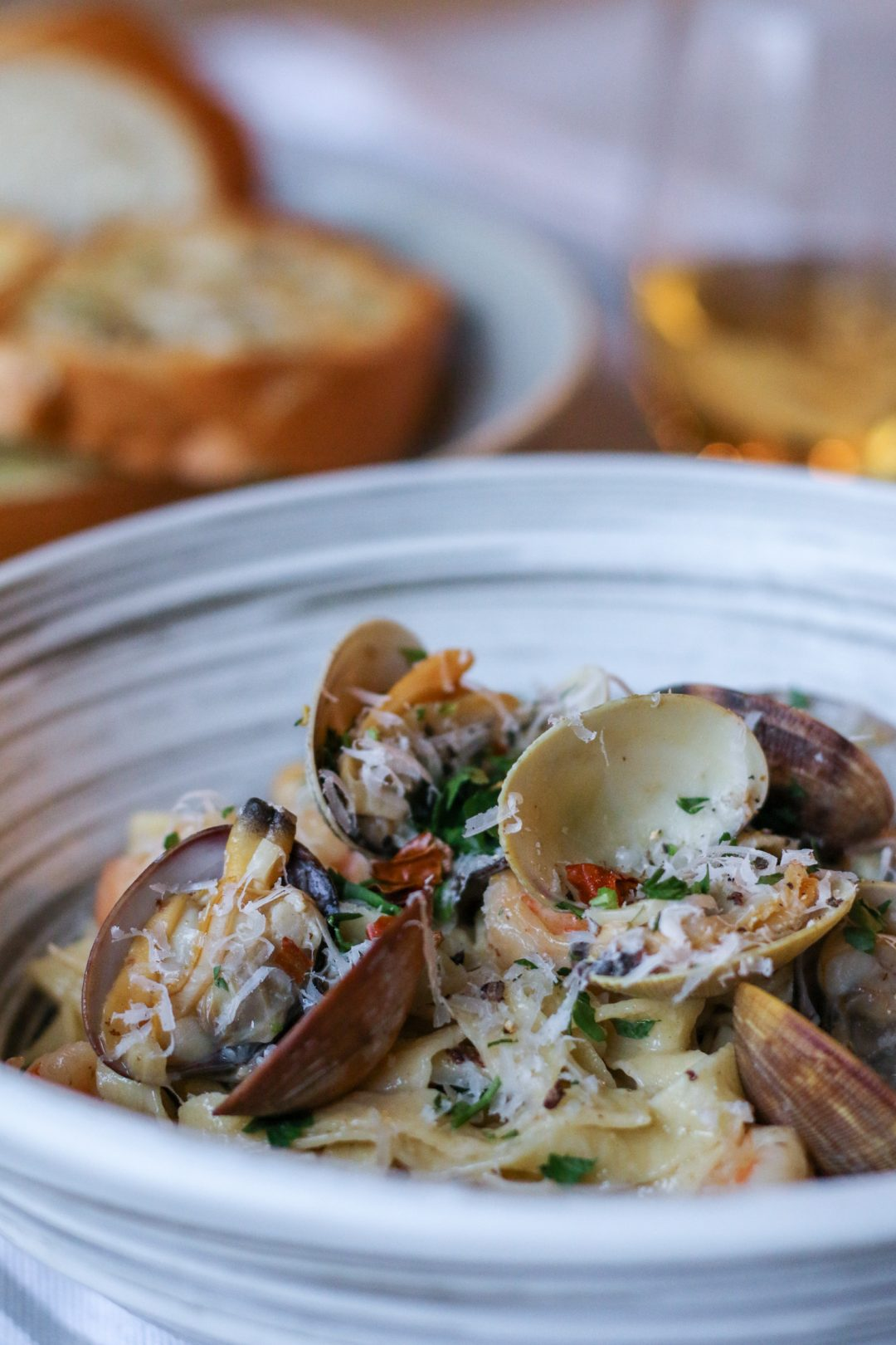 Homemade linguine and clams with creamy white wine sauce and garlic toast